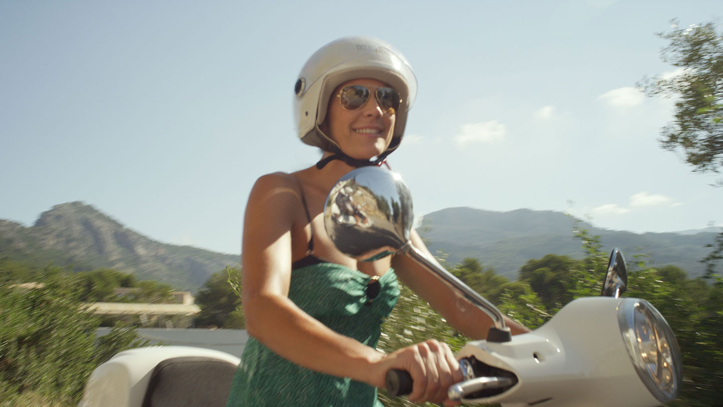 Women riding a vespa in Port Soller mountains